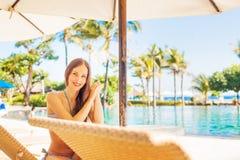 Frau, die nahe einem Swimmingpool sich entspannt Lizenzfreie Stockfotografie