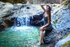 Frau, die nahe einem Wasserfall sitzt Stockbild