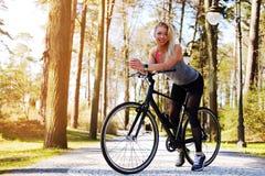Frau, die nahe Fahrrad aufwirft Stockbild