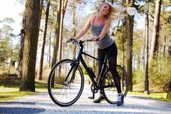 Frau, die nahe Fahrrad aufwirft Stockfoto