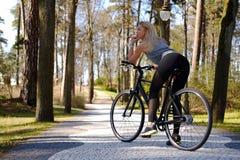 Frau, die nahe Fahrrad aufwirft Stockfotografie