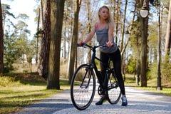 Frau, die nahe Fahrrad aufwirft Lizenzfreies Stockbild