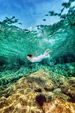 Frau, die nahe Felsen schwimmt Stockfotos