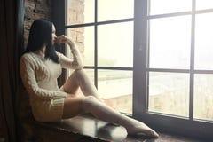 Frau, die nahe Fenster sitzt und draußen schaut Lizenzfreies Stockbild