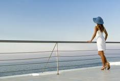 Frau, die nahe Geländer steht und weit schaut Lizenzfreies Stockfoto