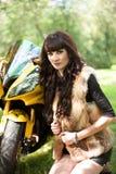 Frau, die nahe ihrem Motorrad sitzt Lizenzfreie Stockfotografie