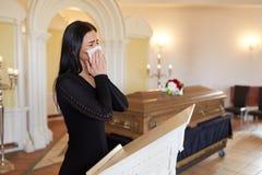 Frau, die nahe Sarg am Begräbnis in der Kirche schreit Lizenzfreies Stockbild