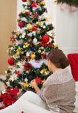 Frau, die nahe sitzt und Weihnachtsbaum verziert Lizenzfreie Stockfotos
