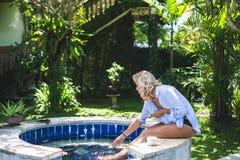 Frau, die nahe Swimmingpool im Garten sitzt Stockfotografie