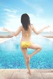 Frau, die nahe Swimmingpool meditiert Lizenzfreie Stockfotografie