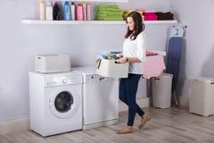 Frau, die nahe Waschmaschine mit Korb von Kleidung steht lizenzfreie stockfotos
