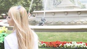Frau, die nahe Wasserbrunnen im Stadtpark aufwirft stock footage