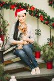 Frau, die nahe Weihnachtsbaum sitzt im roten Hut stockfotos