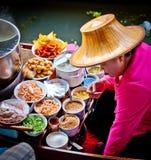 Frau, die Nahrung in Bangkok-sich hin- und herbewegendem Markt kocht Stockfoto