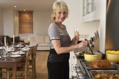 Frau, die Nahrung für ein Abendessen zubereitet stockfoto
