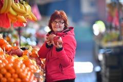 Frau, die NAR-Frucht am Marktplatz kauft Lizenzfreie Stockbilder