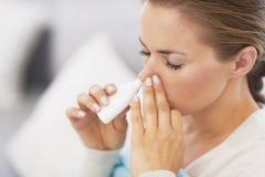 Frau, die nasale Tropfen verwendet Lizenzfreie Stockfotografie