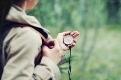 Frau, die Natur entdeckt und Richtungen mit Kompass herein überprüft Stockfotografie