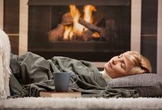Frau, die neben Kamin schläft Stockfotos