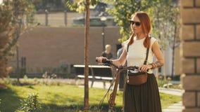 Frau, die neben Reitfahrrad auf Stadtpark geht Frauenfahrradpark lizenzfreies stockbild