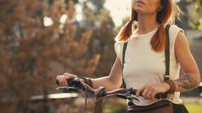 Frau, die neben Reitfahrrad auf Stadtpark geht Frauenfahrradpark lizenzfreie stockbilder