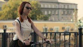 Frau, die neben Reitfahrrad auf Stadtpark geht Frauenfahrradpark stockfoto