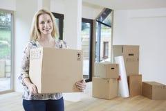 Frau, die in neues Haus mit Verpackungs-Kasten umzieht stockfoto