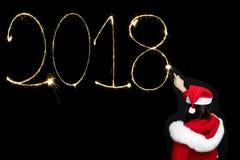 Frau, die 2018 neues Jahr durch Wunderkerze zeichnet Lizenzfreie Stockfotografie
