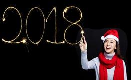 Frau, die 2018 neues Jahr durch Wunderkerze zeichnet Lizenzfreies Stockbild