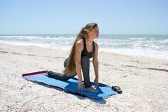 Frau, die niedrige Laufleinehaltung der Yogaübung auf Strand tut Stockfotografie