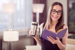 Frau, die Notizbuch betrachtet und Thermo Becher hält stockbilder