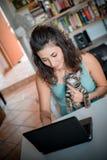 Frau, die Notizbuch mit Katze verwendet Lizenzfreie Stockfotos