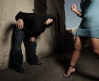 Frau, die oben den Angreifer schlägt Stockfotografie