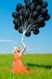 Frau, die oben den schwarzen Ballonen betrachtet Lizenzfreie Stockfotos