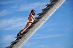 Frau, die oben eine hölzerne Leiter klettert Stockfoto