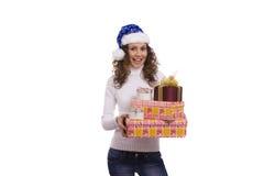Frau, die oben im Weihnachtsschutzkappen-Holdinggeschenk ankleidet lizenzfreie stockfotografie