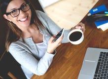 Frau, die oben lächelnd schaut, Handy halten Lizenzfreies Stockbild