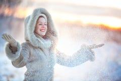 Frau, die oben Schnee wirft Lizenzfreie Stockbilder
