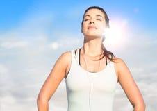 Frau, die oben Sonne gegen sonnigen Himmel mit Aufflackern tränkt Stockbild