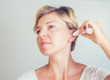 Frau, die Ohrentropfen auf grauem Hintergrund verwendet lizenzfreie stockfotos