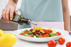 Frau, die Olivenöl auf Gemüsesalat gießt Lizenzfreie Stockfotos