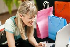 Frau, die online über Internet vom Haus kauft Lizenzfreie Stockbilder