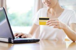 Frau, die online mit einer Kreditkarte und einem Telefon kauft Stockfotos
