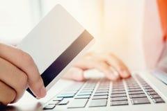 Frau, die online unter Verwendung des Laptops mit der Kreditkarte herein genießt kauft Lizenzfreie Stockfotografie
