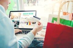 Frau, die online unter Verwendung des Laptops mit der Kreditkarte herein genießt kauft Lizenzfreies Stockfoto