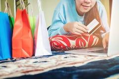 Frau, die online unter Verwendung des Laptops mit der Kreditkarte herein genießt kauft Lizenzfreie Stockfotos