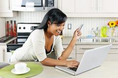 Frau, die online zu Hause kauft Stockfoto