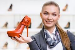 Frau, die orange Lederschuh hält lizenzfreie stockfotos
