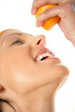 Frau, die Orange in Mund zusammendrückt Lizenzfreie Stockbilder