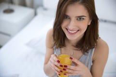 Frau, die Orangensaft auf dem Bett trinkt Lizenzfreie Stockfotos